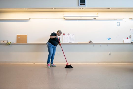 Lorna Bryant, a custodian with RNA Facilities Management, sweeps the floor inside a Renaissance high school classroom, which was being cleaned due to the coronavirus, April 2, 2020.