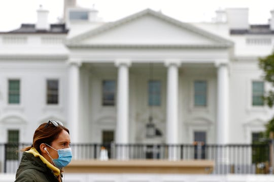 A woman wearing a face mask walks past the White House, Wednesday, April 1, 2020, in Washington. Democrats are zeroing in on health care as one of the few issues that might resonate among Americans who have largely shelved election year politics as they focus on protecting their families from the spreading coronavirus.