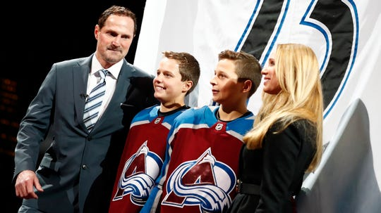 Retired Avalanche forward Milan Hajduk, from left, stands with his sons, Marek and David, and wife, Zlata, during a ceremony to retire Hejduk's number 23 in Denver on  Jan. 6, 2018.