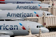 American Airlines jets sit idly at their gates Wednesday, March 25, 2020, at Sky Harbor International Airport in Phoenix.