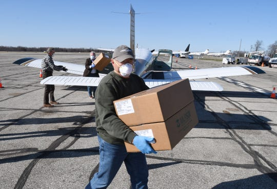Volunteer pilot Curt Martin unloads boxes after returning from a round trip flight to Muncie, Indiana to pick up medical face shields for Michigan health care workers at Willow Run Airport in Ypsilanti, Michigan on April 3, 2020.