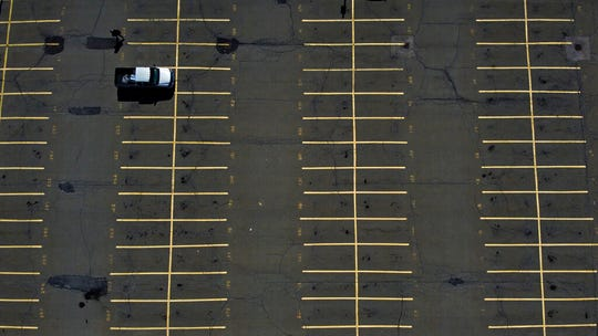A driver walks to catch the train toward Boston after parking in the unusually empty lot for commuters Wednesday, March 18, 2020, in South Attleboro, Mass.