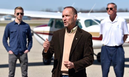 Oakland County Executive David Coulter, center, gives his daily COVID-19 updated on Facebook Live in front of pilots Josh Fenwick, left, and Cran Jones, co-owner of Michigan Seaplane flight school.