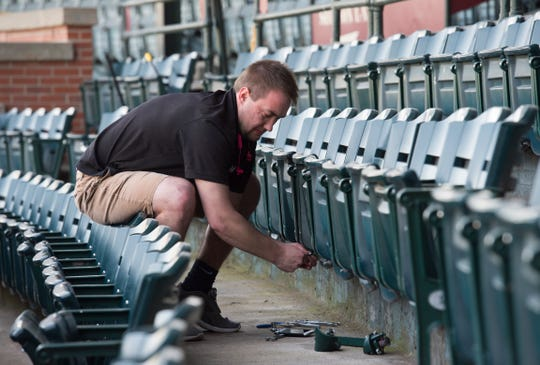 Kyle Gogo tightens up loose seats at historic Bosse Field Thursday afternoon, April 2, 2020.