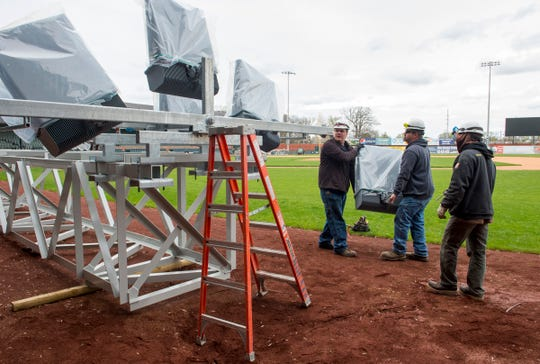 Electricians with Mounts Electric install new LED lights on a light tower that will be placed above the grandstand at historic Bosse Field in Evansville, Ind., Tuesday afternoon, March 31, 2020.