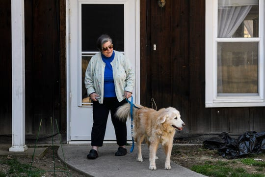 Nancy Lybarger brings her 13-year-old dog Blue outside after getting home from work at the Newburgh Senior Center in Downtown Newburgh, Ind., Wednesday, April 1, 2020. She is the manager of the senior center, which is currently closed to the public due to the COVID-19 pandemic.