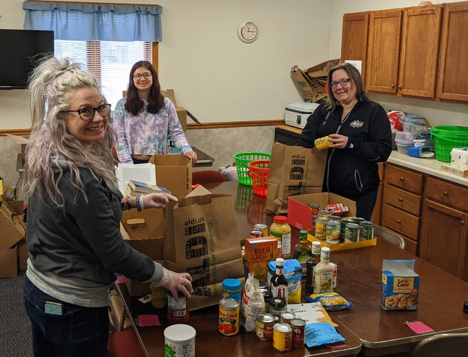 From left, Alicia Hans, Abby Greenfield and Charlotte Hoffman-Trotter pack care packages to be distributed to those in need through the group, CORE Ambassadors for Change.