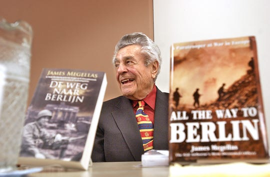 """Jim Megellas listens as he is introduced to speak about his book, """"All the Way to Berlin,""""  in 2016 at the Fond du Lac Public Library. The book translation into Dutch is on the left."""