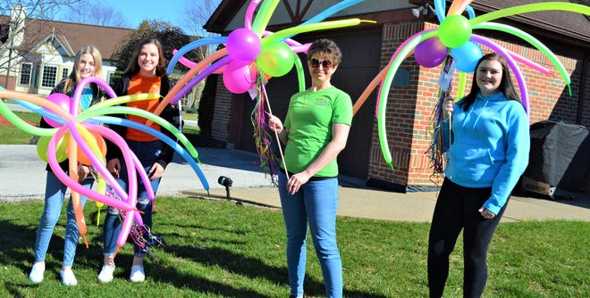 Kristy Reiter, second from right, and her daughters surprised residents of Elmwood Centers' group homes with outdoor balloon arrangements on April 2. With her are, from left, Corinne, Katie, and Andrea.