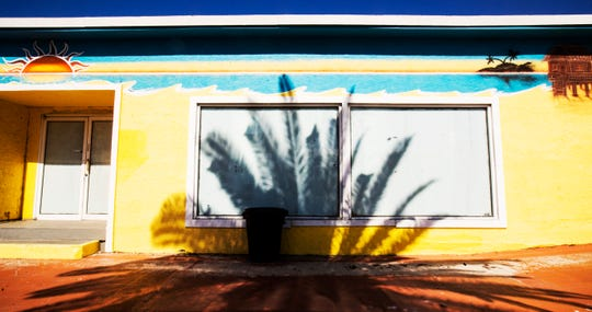 A shadow from a palm tree is cast on a closed Fort Myers Beach business on Friday, April 3, 2020. The building will be part of the Margaritaville resort that will eventually be built. The resort hit another speed bump as oral arguments in the case will now be delayed due to COVID-19 after being scheduled for the 15th of this month. The developer and the town asked the court not to reschedule it but the court decided to grant the petitioner, Chris Patton's, request to reschedule the argument and move forward at an undetermined date.