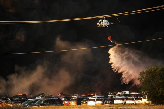 A helicopter sprays an out of control fire near Southwest Florida International Airport on Friday April 3, 2020.