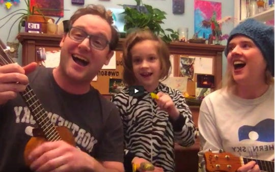 """Northern Sky Theater company members Chase Stoeger and Molly Rhode, joined by their daughter, Silvia, sing """"The Possum Trot"""" from the Paul Libman/Dave Hudson musical """"Naked Radio"""" from their Milwaukee home in this still shot from the first in the """"Northern Sky at Home"""" online video series."""