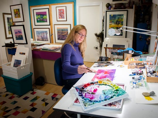 Artist Lynn Greer paints in her home studio in Greenville.