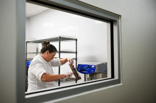 Elizabeth McDaniel scrapes excess chocolate from a mold at LaRue Fine Chocolates Friday, April 3, 2020. McDaniel decided to open LaRue, in the making for three years, despite the challenges of operating a business amid the novel coronavirus pandemic.