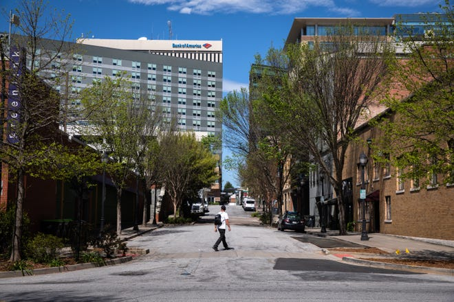 A man walks through a subdued Downtown Greenville as a result of the coronavirus outbreak, Friday, April 3, 2020.