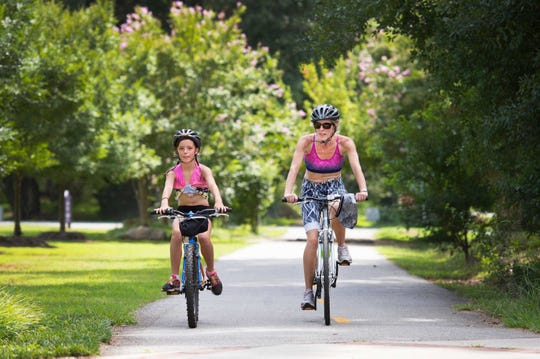 Jo Williams and her daughter Zoe, 9, bike down the Swamp Rabbit Trail near Furman University on Tuesday, August 23, 2016. They were visiting Greenville from England and said they have nothing like the trail there.