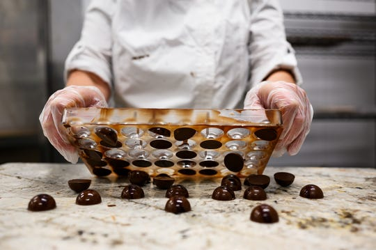 Elizabeth McDaniel shakes chocolate from a mold at LaRue Fine Chocolates Friday, April 3, 2020. McDaniel decided to open LaRue, in the making for three years, despite the challenges of operating a business amid the novel coronavirus pandemic.