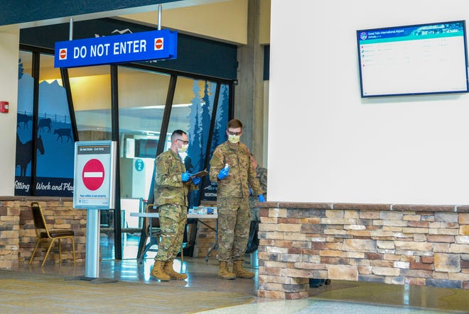 Members of the Montana Air National Guard's 219th Red Horse Squadron do temperature checks of airline passengers arriving at Great Falls International Airport on Friday, April 3, 2020.