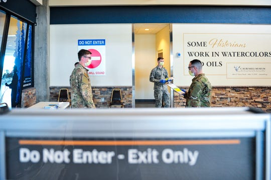 Members of the Montana Air National Guard's 219th Red Horse Squadron prepare to do temperature checks of airline passengers arriving at Great Falls International Airport on Friday, April 3, 2020. Members of the Montana Air National Guard will be used in 11 cities and 17 locations statewide to screen people arriving in Montana by air or rail in response to COVID-19 concerns.