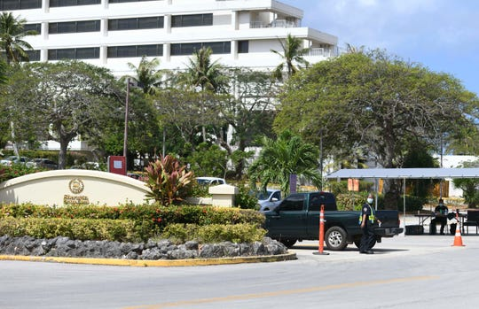 A G4S Security officer allows a vehicle to proceed beyond a checkpoint at the parking lot entrance to the Sheraton Laguna Guam Resort in Tamuning on Friday, April 3, 2020.