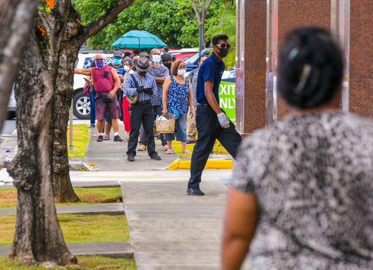 Patrons stand in a long line, due in part to social distancing measures implemented at the Bank of Guam, Hagåtña Branch, as the wait to gain entry to the bank's lobby and service by one of the tellers inside on Friday, April 3, 2020.