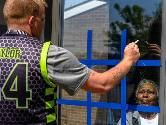 Resident Glendora Bostick watches as Kevin Taylor makes his move during a game of tic-tac-toe through a window as members of the semi-pro Henderson Hornets basketball team play tic-tac-toe and paint windows with residents of Redbanks Colonial Terrace Nursing Center Friday.
