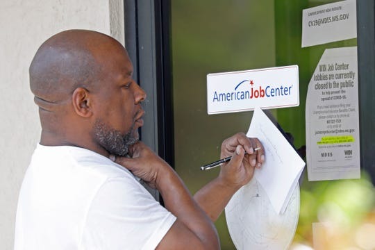 A resident copies down the Mississippi unemployment benefit website after being unable to enter the state WIN Job Center in north Jackson, Miss., Thursday, April 2, 2020. The job centers lobbies are closed statewide to prevent the spread of COVID-19. The agency encourages residents to apply for their benefits on line. Some centers have made paper unemployment applications available to those people without computers, for them to mail back or push through the centers' mail slots or doors.