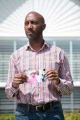 Anthony Ragland holds a photo of his father, Tommy Felder, outside his home in Knoxville on Friday, April 3, 2020. Felder died Monday in New York after contracting the coronavirus.