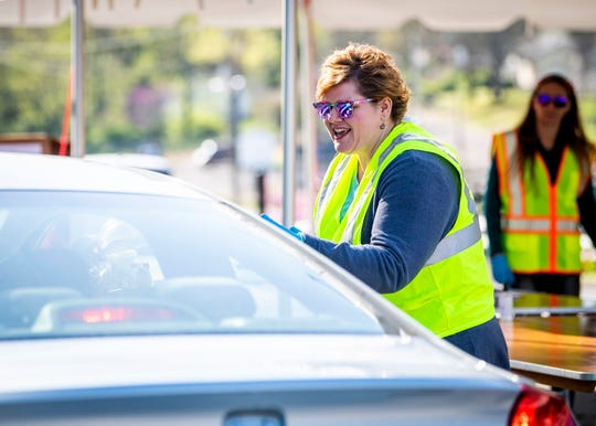 Kyndra Brewer with the City of Knoxville's Office of Special Events collects PPE from a donor at a drive-thru donation spot at the Jacob Building in Knoxville's Chilhowee Park on Friday, April 3, 2020. The Personal Protective Equipment Collection Drive kicked off on Friday and will held on Mondays, Wednesdays and Fridays from 9 a.m. to 3 p.m. Donated PPE will be distributed to first responders in Knoxville and Knox County.