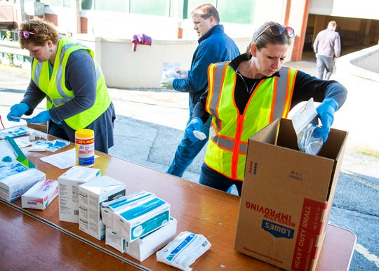 Elaine Frank, right, with the City of Knoxville's Office of Special Events, sanitizes then sorts donated masks at the Jacob Building at Knoxville's Chilhowee Park on Friday, April 3, 2020. The Personal Protective Equipment Collection Drive kicked off on Friday and will held at the Jacob Building at Chilhowee Park on Mondays, Wednesdays and Fridays from 9 a.m. to 3 p.m. Donated PPE will be distributed to first responders in Knoxville and Knox County.