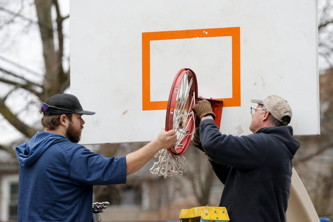 James Smith, left, and Douglas Roak, both with the West Lafayette Parks and Recreation department, dismantle a basketball hoop at Tommy Johnston Park, Friday, April 3, 2020 in West Lafayette.