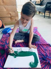 Monroe, a kindergartener at Martial F. Billeaud Elementary in Broussard, paints at home during Virtual Art Day hosted by the school.