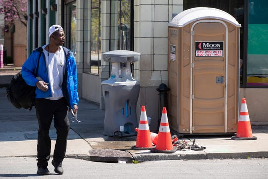 A pedestrian makes their way past a portable bathroom and hand washing station at First Street and Broadway on Friday.