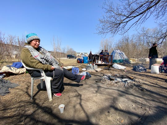 Amanda Koehler talks about how she had trouble sleeping in a tent at a homeless camp the previous night, located near N. Larch and Saginaw Street in Lansing,  Friday afternoon, April 3, 2020.  Koehler is seven-months pregnant, and says she's there because she had to leave an abusive relationship.  She says she's having trouble finding a place to stay, and that shelters are full due to the COVID-19 coronavirus pandemic.
