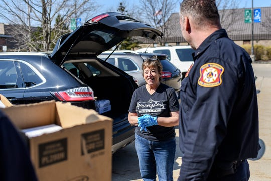 MorningLory Cafe & Bakery owner Lori Conarton, left, smiles while talking with Delta Township Fire Department Lt. Brian Hatfield, right, after she delivered 45 chicken pot pies and notes of support from the community on Friday, April 3, 2020, at the Delta Township Fire Station. Volunteers delivered 125 pies and cards to first responders in Delta, Windsor, Benton and Delhi townships and the city of Grand Ledge. Lori aims to deliver the pot pies every Friday until state coronavirus orders are lifted.