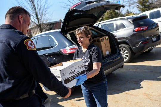 MorningLory Cafe & Bakery owner Lori Conarton, right, delivers 45 chicken pot pies and notes of support from the community to Delta Township Fire Department Lt. Brian Hatfield on Friday, April 3, 2020, at the Delta Township Fire Station. Volunteers delivered 125 pies and cards to first responders in Delta, Windsor, Benton and Delhi townships and the city of Grand Ledge. Conarton aims to deliver the pot pies every Friday until state coronavirus orders are lifted.