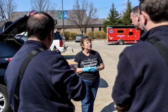 MorningLory Cafe & Bakery owner Lori Conarton, center, talks with Delta Township Fire Department Lt. Brian Hatfield, right, after she delivered 45 chicken pot pies and notes of support from the community on Friday, April 3, 2020, at the Delta Township Fire Station. Volunteers delivered 125 pies and cards to first responders in Delta, Windsor, Benton and Delhi townships and the city of Grand Ledge. Lori aims to deliver the pot pies every Friday until state coronavirus orders are lifted.