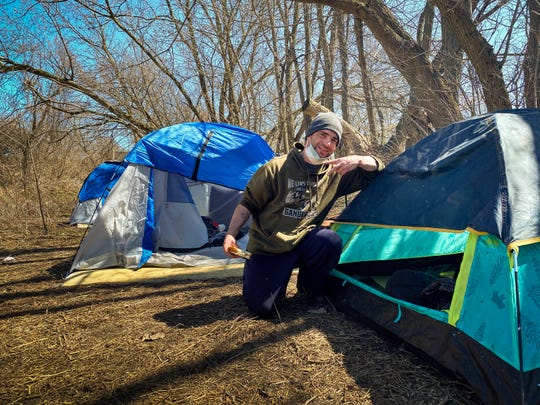 Jason Ells poses for a portrait outside his tent, Thursday, April 2, 2020, at a homeless camp near N. Larch and Saginaw Streets in Lansing.  Local advocate Candice Wilmore reached out to people via social media pleading for others to help her help the homeless, and the community stepped up.  Tents and mats were donated or sold at a discount, and during the COVID-19 pandemic, officials from the CDC have recommended that camps like this not be broken up.