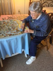 Velma Cox works on a puzzle