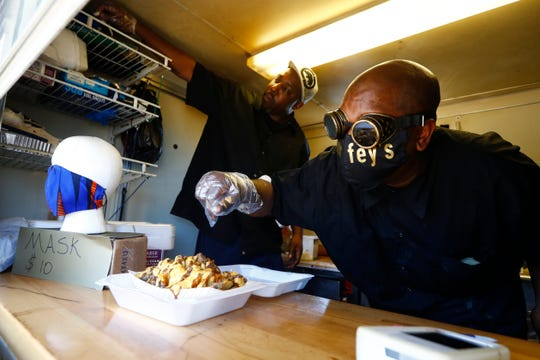 Kendrick Westbrook, right, owner of Smurfey's Smokehouse food truck, and his brother Gregory work inside their kitchen on Thursday, April 2, 2020. Multiple food trucks, including Smurfey's, have said they will be serving from the parking lot on Union Avenue and South Watkins Street, Monday through Friday from 11am-5pm.