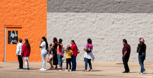 Customers stand in line outside of the Atlanta Highway Walmart after new social distancing guidelines in Montgomery, Ala., on Friday April 3, 2020.