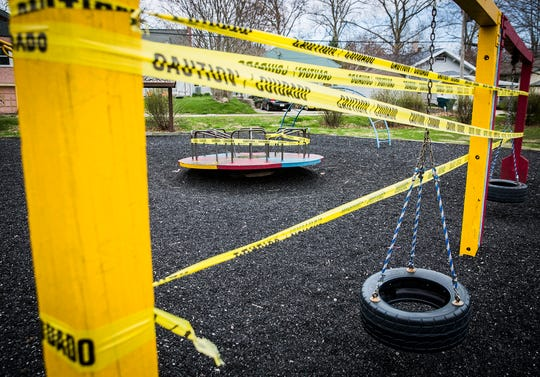 Caution tape is secured around playground equipment at Tuhey Park in Muncie to prevent the spread of coronavirus.