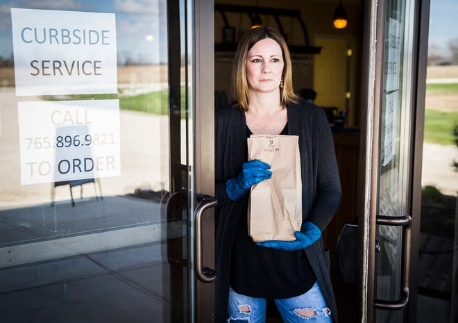 """Sara Rogers takes """"drive thru"""" orders at Tonne Winery Thursday, April 2, 2020. The Muncie winery is taking curbside to-go orders to alleviate some of the financial burden created by the coronavirus pandemic."""
