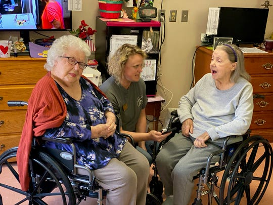 Community Care of Rutherford County employee Mary Beth Bayman, center, sings with residents Betty Sneed, left, and Donna Keene.