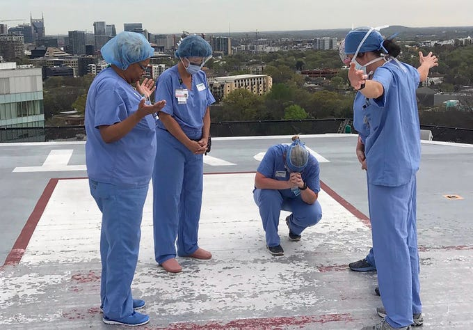 From left, Vanderbilt staff members Tanya Dixon, ORT; Beth Tiesler, ORT; Sarah Kremer, RN; Angela Gleaves, RN; and McKenzie Gibson, RN, pray on the hospital's helipad. Kremer asked her group of nursing friends to celebrate her birthday by praying with her.