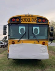 Masked Dickson County School bus promotes proper COVID-19 precaution in front of the school district's transportation department.