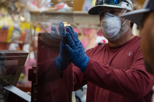 Wynn Properties maintenance workers Miguel Muniz, left, and maintenance supervisor Brian Galarza install a plexiglass shield at a register, Friday, April 3, 2020, at Wynn's Market in Naples.