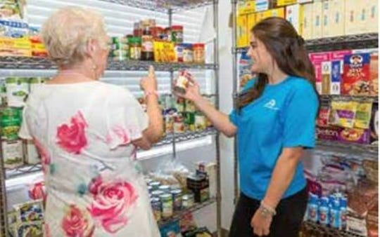 Volunteers work to stock the Naples Senior Center food pantry.