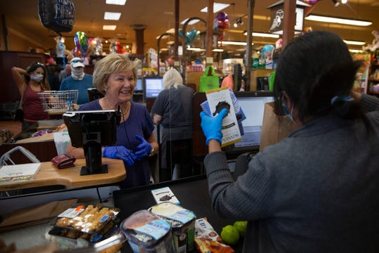 Customer Jody Ford a Naples seasonal resident from Baltimore, Maryland, talks with Wynn's cashier Lisa Burlinson, as she pays for her groceries, Friday, April 3, 2020, at Wynn's Market in Naples. Wynn's Market installed plexiglass shields to protect customers and employees from the coronavirus.