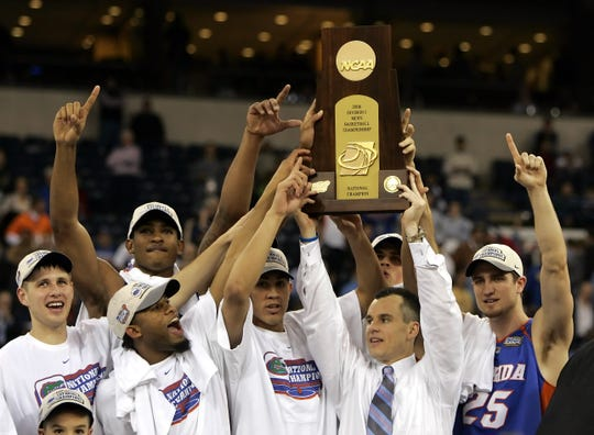 In this April 3, 2006, file photo,  Florida players celebrate as head coach Billy Donovan holds their trophy aloft after beating UCLA 73-57 in the NCAA national championship basketball game in Indianapolis.